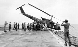 Le 29 avril 1975, des membres de l'équipage de l'USS Blue Ridge font basculer un hélicoptère dans la mer pour faire plus de place aux personnes évacuées de Saïgon (Photo : SIPA.AP21728262_000012)
