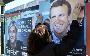Une militante colle l'affiche de campagne d'Emmanuel Macron à Saint-Jean-de-Luz, avril 2017. SIPA. AP22045457_000033