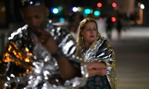 """Des passants, enveloppés dans des couvertures de survie, quittent le London Bridge, au centre de Londres, le 3 juin 2017, où une camionnette a foncé sur la foule. La police parle d'un acte """"terroriste"""".  © AFP Chris J Ratcliffe"""