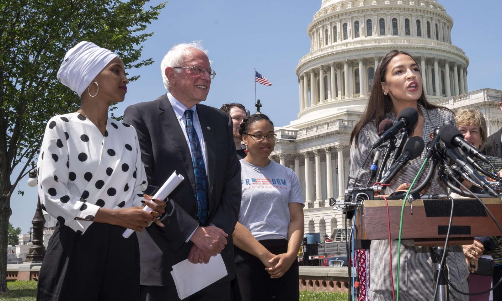 A gauche, les démocrates Ilhan Omar (avec le foulard) et Bernie Sanders. Devant les micros, la démocrate Alexandria Ocasio-Cortez. Le 24 juin 2019 à Washington. © J. Scott Applewhite/AP/SIPA Numéro de reportage: AP22350636_000005