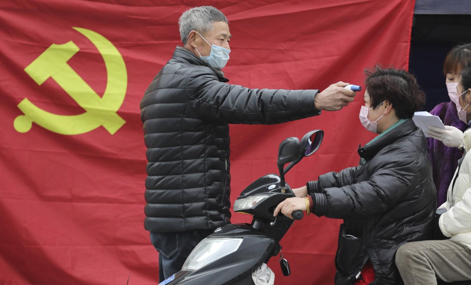 En février 2020, à Hangzhou (Est de la Chine), un volontaire prend la température d'un conducteur de scooter © AP/SIPA Numéro de reportage: AP22425472_000001