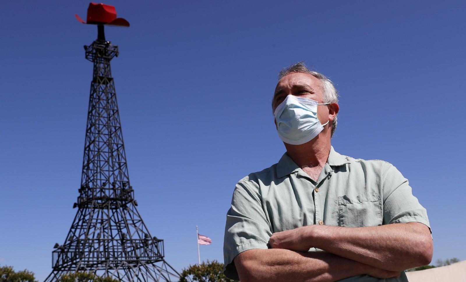 Le maire de Paris (Texas) Steve Clifford pose devant la petite Tour Eiffel de la ville, mercredi 29 avril 2020. © AP Photo/Tony Gutierrez