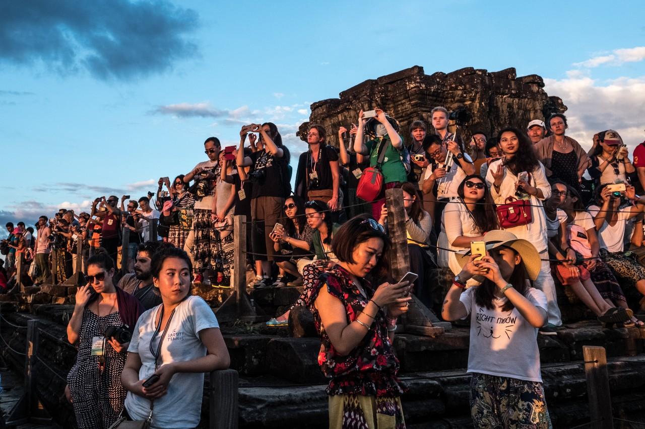 Des touristes photographient le coucher de soleil depuis l'un des temples d'Angkor, Cambodge, 23 décembre 2016 © Jonathan Fontaine / Hans Lucas / AFP