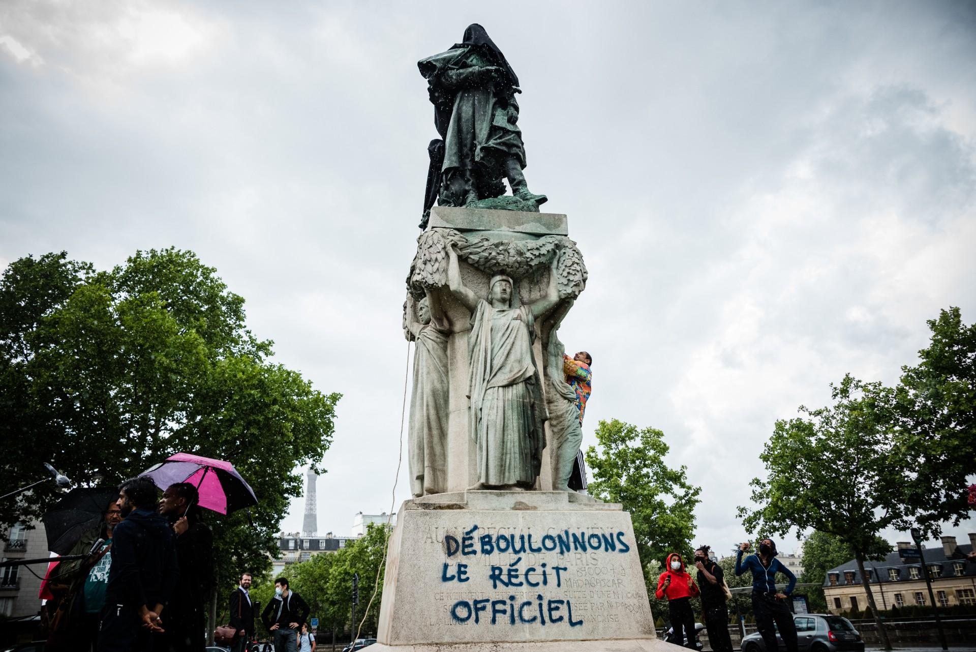 Vikash Dhorasoo et une vingtaine de militants antiracistes recouvrent d'un voile noir la statue du maréchal galliéni, héros de la Première Guerre mondiale et administrateur colonial français, Paris, 18 juin 2020. © J. Radcliffe/Getty Images/AFP