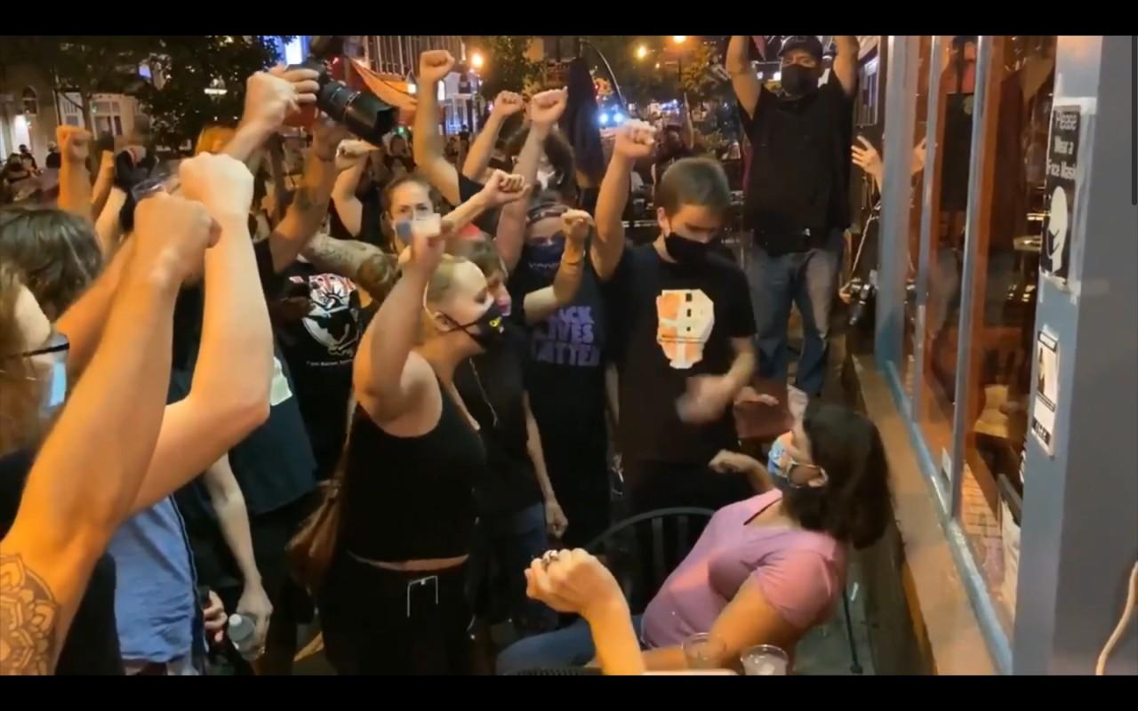Malgré la pression de la foule, une cliente d'un restaurant refuse de lever le poing en signe de soutien au mouvement Black Lives Matter, Washington D. C., 25 août 2020. D.R.