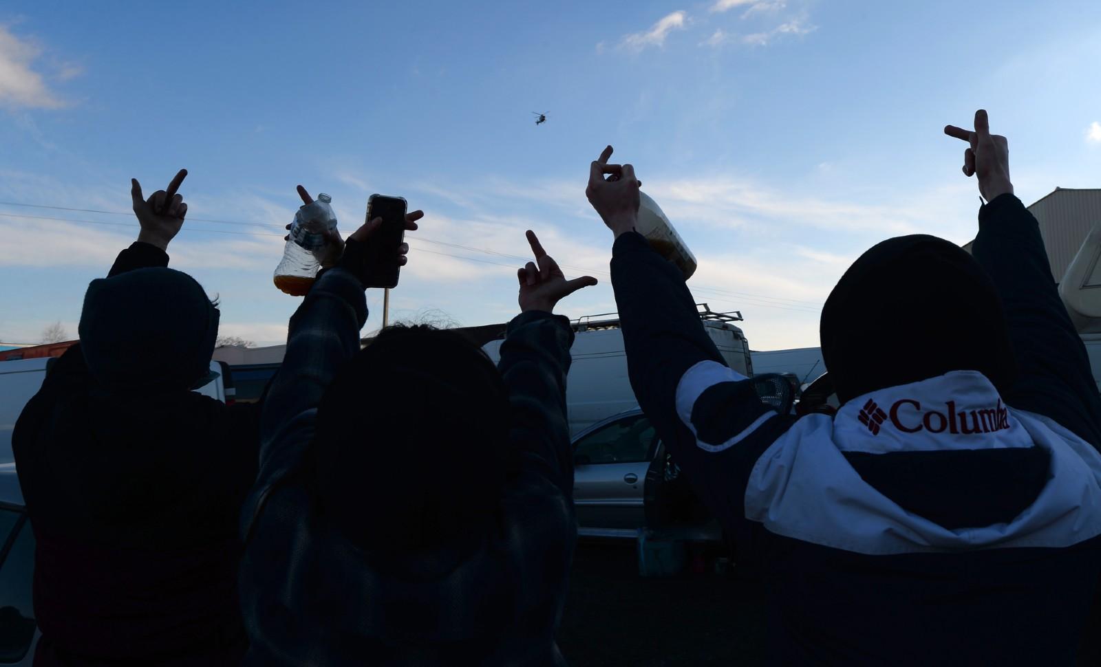 Le 1er janvier 2021, à Lieuron (Ille-et-Vilaine), à environ 40km de Rennes, des jeunes participant à une rave party adressent des doigts d'honneur aux gendarmes © JEAN-FRANCOIS MONIER / AFP.
