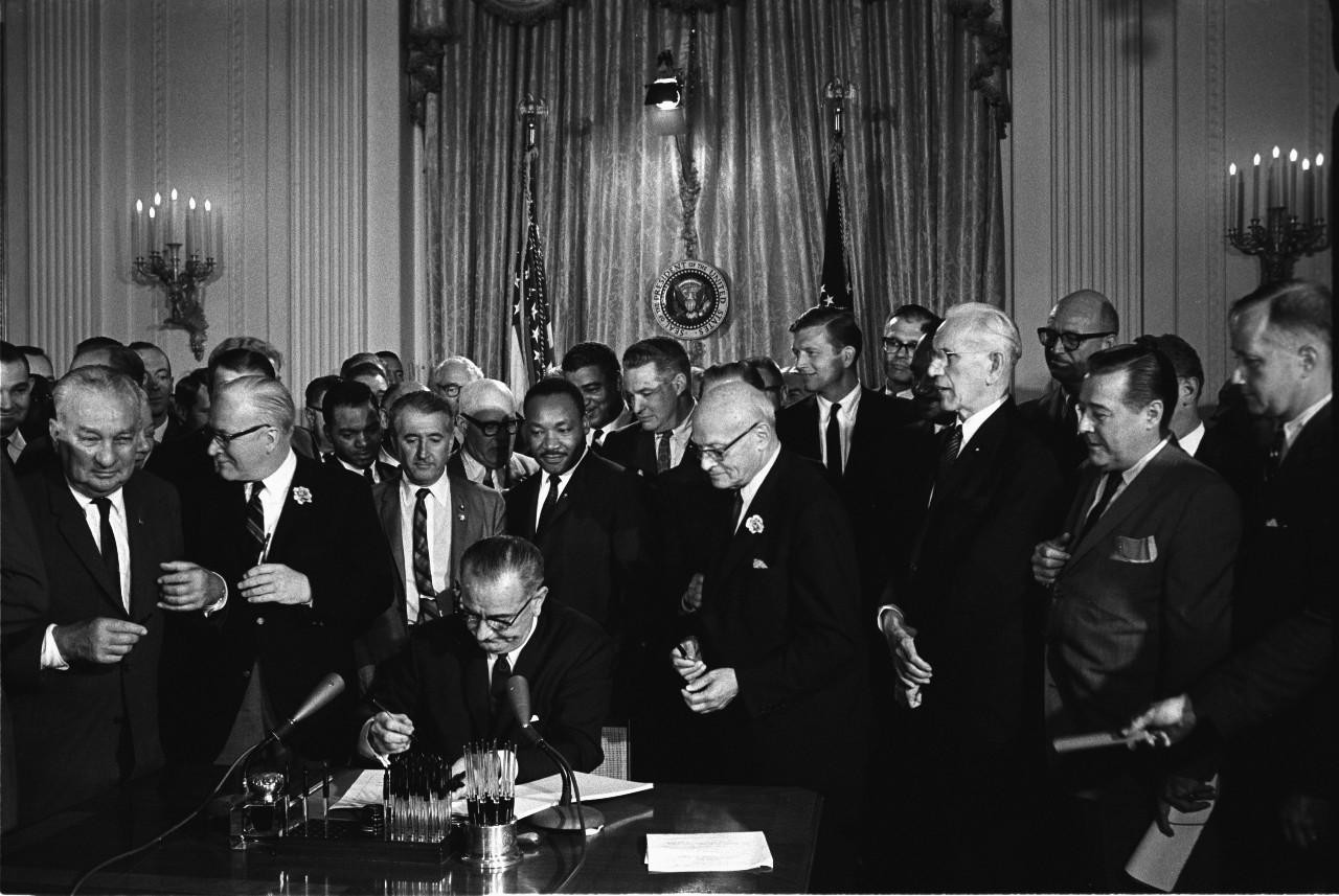 Signature du Civil Rights Act par Lyndon B. Johnson, en présence de Martin Luther King et de militants des droits civiques, Maison-Blanche, 2 juillet 1964. © Wikimedia