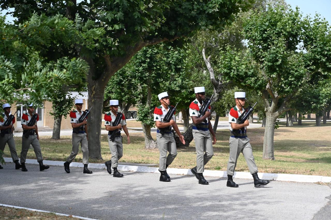 """Pendant que leurs chefs sont en plein rituel """"boudin-vin blanc"""" (voir photos suivantes), de jeunes légionnaires en tenue de parade s'en vont former un piquet d'honneur pour saluer le départ d'un officier du régiment."""